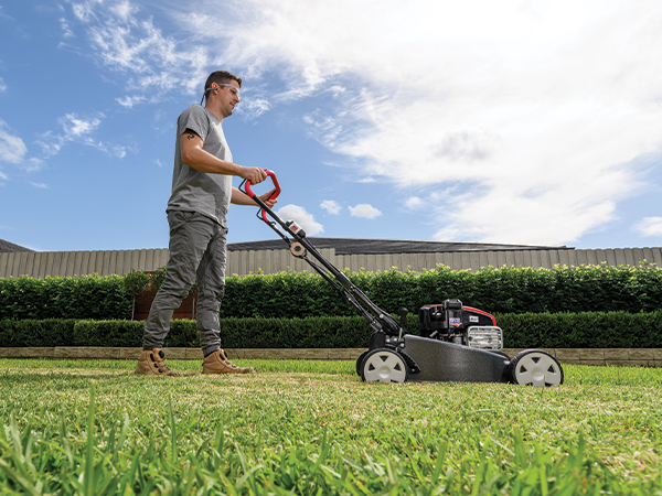 Man cutting grass with lawn mower
